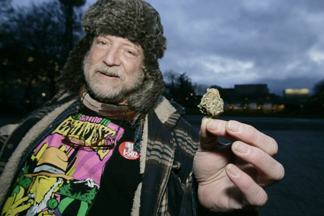 Michael Dare, a medical marijuana user, displays a bud during a public consumption of marijuana rally at the Seattle Center on December 6, 2012 in Seattle. Despite the new law's ban on public marijuana use which is subject to a fine of about $50.00 many showed up for the smoke-in. In November, Washington state jumped into history becoming the first state along with Colorado to reject federal drug-control policy and legalize recreational marijuana use. UPI/Jim Bryant
