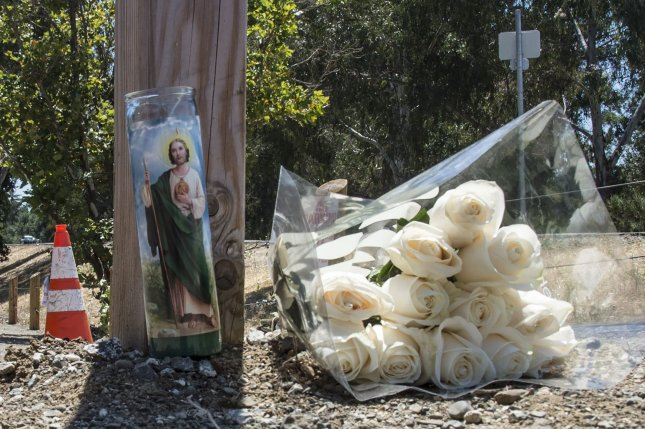 A boquet of roses and a candle are seen July 29 at the entrance to the Gilroy Garlic Festival in Gilroy, Calif. Photo by Terry Schmitt/UPI
