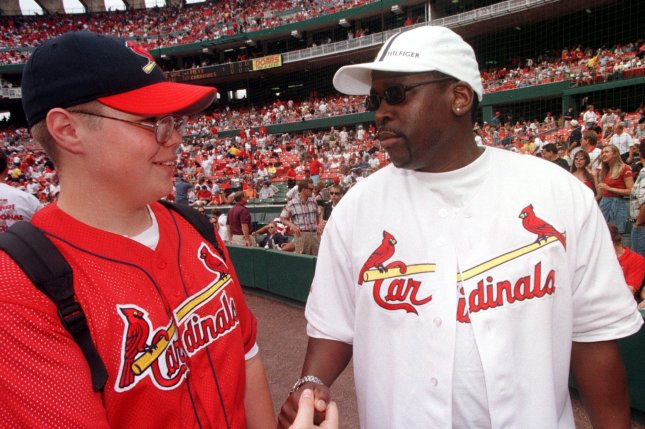 Dearon Deezer D Thompson (R) greets Cardinal fan Jon Kempker on the field, prior to a game between the St. Louis Cardinals' and the New York Mets' in 1999. He died Thursday at age 55. File Photoby wy/bg/Bill Greenblatt/UPI