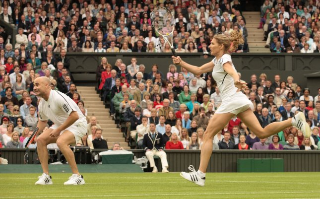 Andre Agassi and wife Steffi Graf play a mixed doubles exhibition match on the new Wimbledon Center Court with the roof fully closed May 17 2009. (UPi Photo/Hugo Philpott)