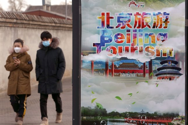 Chinese residents walk along a sidewalk wearing face masks due to the threat of the deadly coronavirus on Friday. Photo by Stephen Shaver/UPI