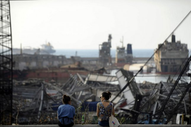 Two women overlook the site of the Beirut port damaged on Aug. 4 by a massive explosion. More than a month later, on Saturday, rescuers detected signs of life again under the rubble. File Photo by Mustafa Jamaleddine/UPI