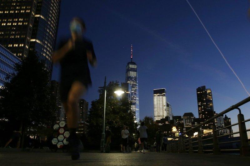 A masked runner jogs along the Hudson River in New York City on Thursday. Photo by John Angelillo/UPI