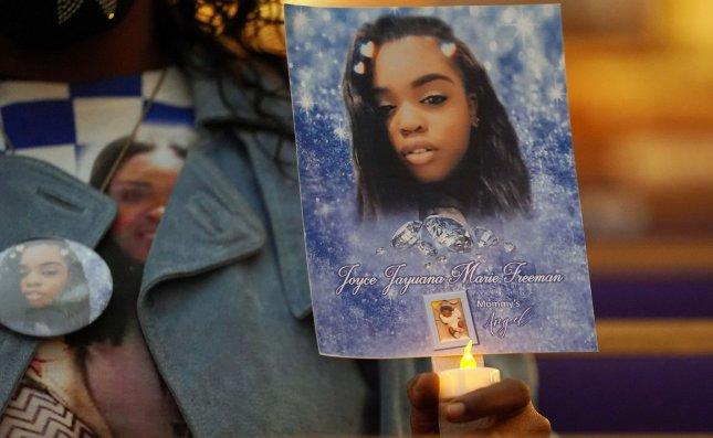 Lataisha Jones-Lewis holds a photo of her daughter Joyce Freeman during a New Year's Eve Candlelight Service commemorating those who lost their lives to violence in 2020. File Photo by Bill Greenblatt/UPI
