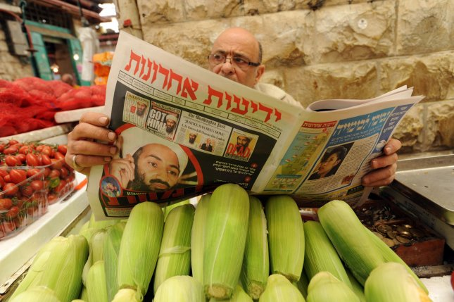 An Israeli vendor reads a Hebrew newspaper in the Mahane Yehuda Market in Jerusalem with headlines announcing the killing of Osama bin Laden by U.S. special forces in Pakistan, May 3, 2011. UPI/Debbie Hill