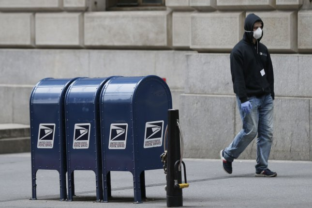 A man wears a protective mask as he passes a row of U.S. Postal Service mailboxes on Wall Street in New York City on March 20. Photo by John Angelillo/UPI
