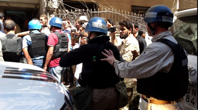 Opposition fighters and civilians stand near members of a United Nations (UN) delegation as UN arms experts inspect the site where rockets fell in Damascus' Eastern Ghouta suburb on August 28, 2013. Rebels who control the area said the inspectors travelled in a six-vehicle convoy to investigate a suspected chemical weapons strike on August 21. UPI/Mohammed Al-Abdullah