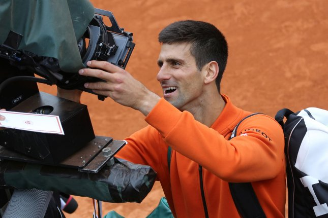 Novak Djokovic of Serbia signs a camera lens after winning his French Open men's first round match against Jarkko Nieminen of Finland at Roland Garros in Paris on May 26, 2015. Djokovic defeated Nieminen 6-2, 7-5, 6-2 to advance to the second round. Photo by David Silpa/UPI