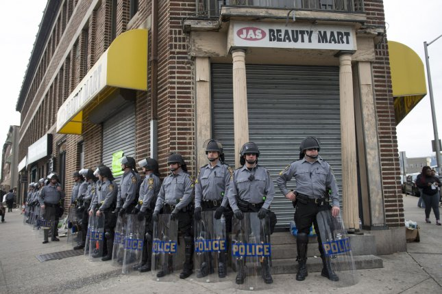 Police stand by in Baltimore during demonstrations May 1, 2015, over the death of Freddie Gray. A Department of Justice report said there is pervasive racism in Baltimore police procedures and unnecessary adversarial intreractions with the community. File Photo by Kevin Dietsch/UPI
