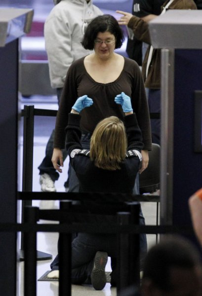 A TSA screener pats down a passenger at a security checkpoint at O'Hare International Airport on November 24, 2010 in Chicago. Security ran smoothly on the day before Thanksgiving despite rumors of mass protests of security procedures. UPI/Brian Kersey