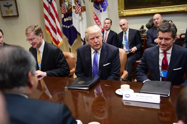 President Donald Trump talks to the heads of American manufacturing corporations at a meeting at the White House on Monday morning. He told the assembled CEOs to expect a dramatic cut in the number of federal regulations, and a penalty for making products outside the United States. Pool photo by Ron Sachs/UPI