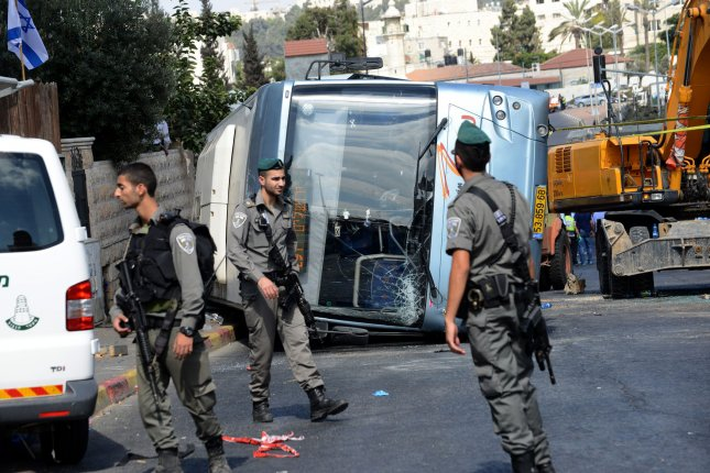 Israeli border police walks in front of an overturned Israeli bus, that was a flipped in a terror attack when a Palestinian rammed a tractor into the bus in Jerusalem, Israel, August 4, 2014. A pedestrian was killed and several hurt in the attack. The driver was shot dead when he kept ramming the bus. UPI/Debbie Hill