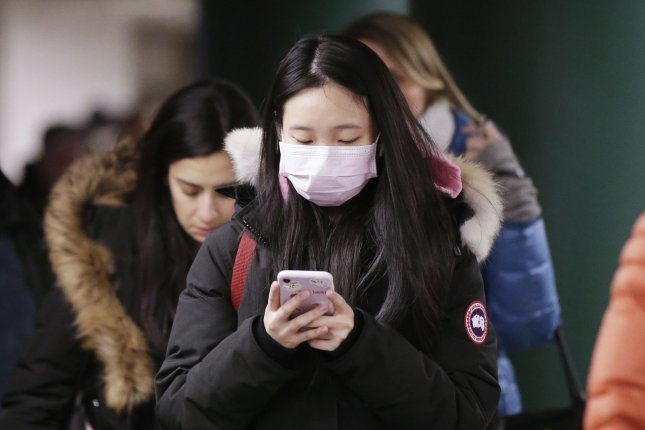 A woman wears a mask covering her mouth and nose while walking through the subway on January 27, 2020, in New York City. The CDC on Monday confirmed there are 11 cases of coronavirus in the United States, as well as the second transmission of the virus from human to human. Photo by John Angelillo/UPI