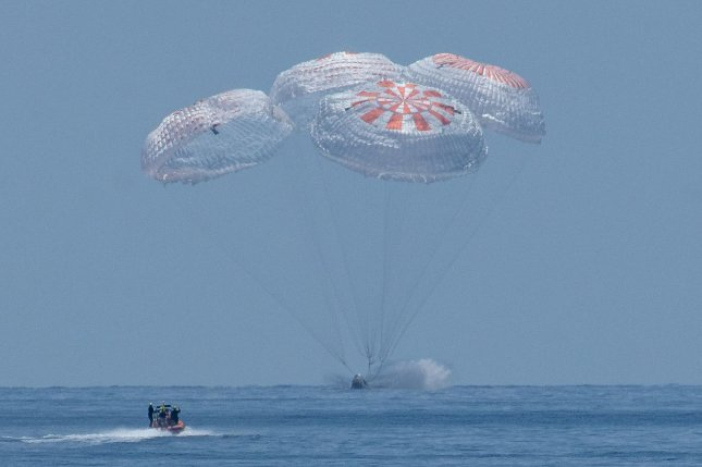 Slowed by four parachutes, the SpaceX Crew Dragon Endeavour lands with NASA astronauts Robert Behnken and Douglas Hurley onboard in the Gulf of Mexico off Pensacola, Fla., on Sunday. NASA Photo by Bill Ingalls/UPI