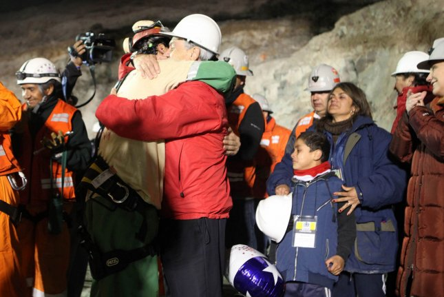 Chilean miner Florencio Avalos, the first of 33 trapped miners to be rescued, hugs President Sebastian Pinera and his son at the surface of the San Jose Mine near Copiapo, Chile, just after midnight October 13, 2010. Photo courtesy the Chilean government