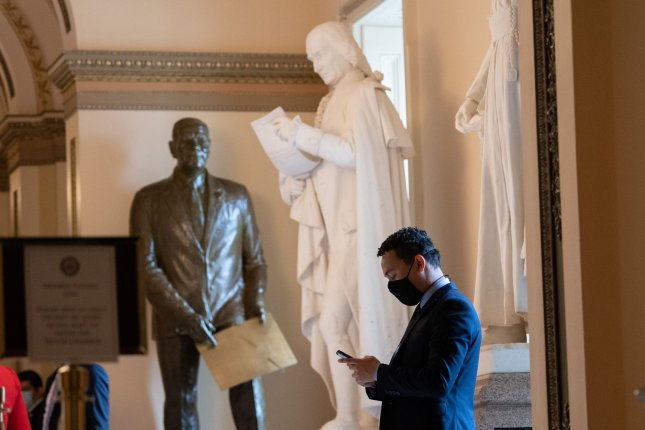 A staffer wears a mask while using a cellphone at the U.S. Capitol in Washington, D.C. in April, ahead of a vote on a coronavirus relief bill. Photo by Kevin Dietsch/UPI