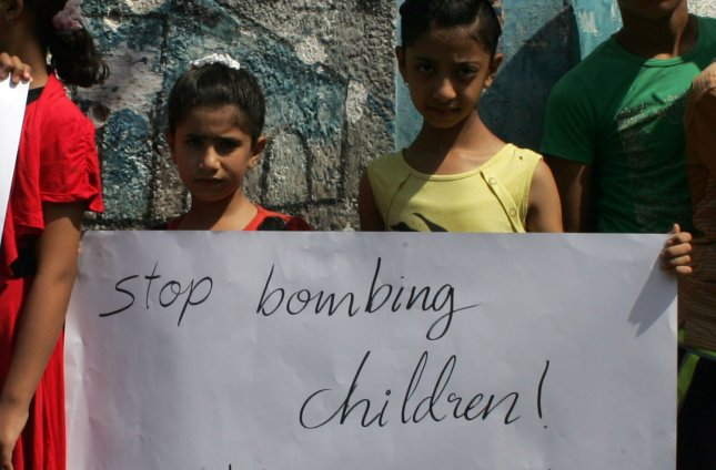 Palestinian children hold posters and banners outside an UNRWA school during a protest against the killing of children on August 10, 2014 in the southern city of Rafah, a week after the school was hit by an Israeli strike, killing at least 10 Palestinians. The school was sheltering Palestinians displaced by the ongoing violence in Gaza. UPI/Ismael Mohamad