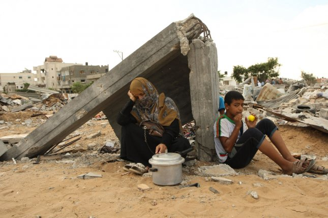 Members of a Palestinian family sit amongst the rubble of their home in Khan Younis that was destroyed by an Israeli air strike during a seven-week war with Gaza, UPI/Ismael Mohamad