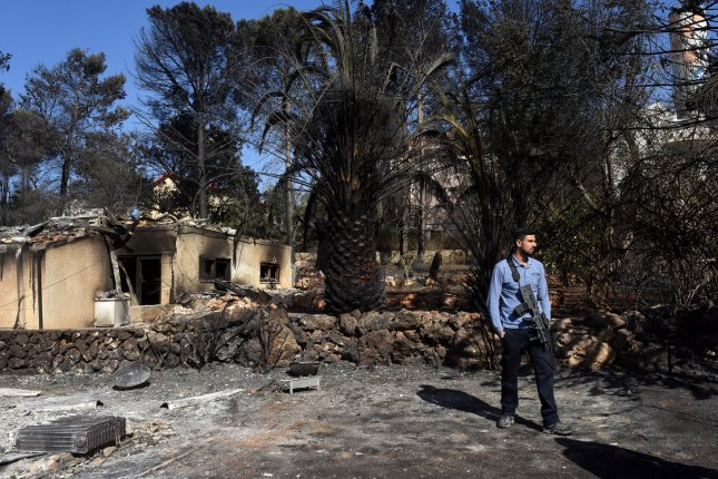 An Israeli stands Sunday by a house destroyed by a fire in the Jewish settlement Hamalish in the West Bank. Several firebombs were found in the area of the settlement where 45 homes were damaged and 18 completely destroyed. Police have arrested 24 suspects in arson cases that have ravished Israel and the West Bank. Photo by Debbie Hill/UPI