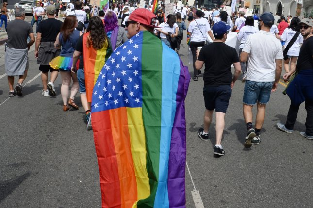 A person marches in the Los Angeles gay pride parade carrying an American flag modified to show the movement's rainbow colors. The U.S. Civil Rights Commission slammed a proposal by President Donald Trump to ban transgenders from serving in the military. File Photo by Jim Ruymen/UPI