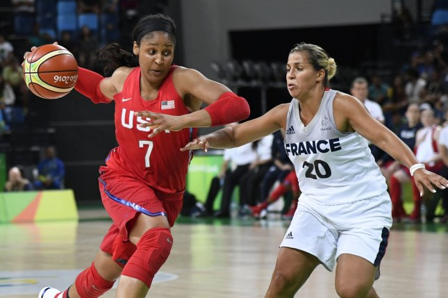 United States basketball star Maya Moore (L) drives to the basket against France's Amel Bouderra at the 2016 Rio Summer Olympics in Rio de Janeiro, Brazil. File Photo by Mike Theiler/UPI