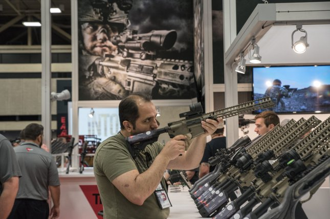 A convention attendee inspects a gun on the floor of the exhibition hall at the 147th National Rifle Association Annual Meetings and Exhibits in Dallas on May 5. Ohio's legislature on Thursday approved broader rights for gun owners, overturning a veto by outgoing Gov. John Kasich, that includes expanded gun access in government subsidized housing. File Photo by Sergio Flores/UPI
