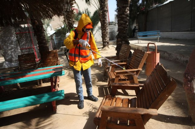 A Palestinian municipality worker wears protective gear while disinfecting a park Wednesday to help prevent the spread of the coronavirus in Rafah southern Gaza. Photo by Ismael Mohamad/UPI