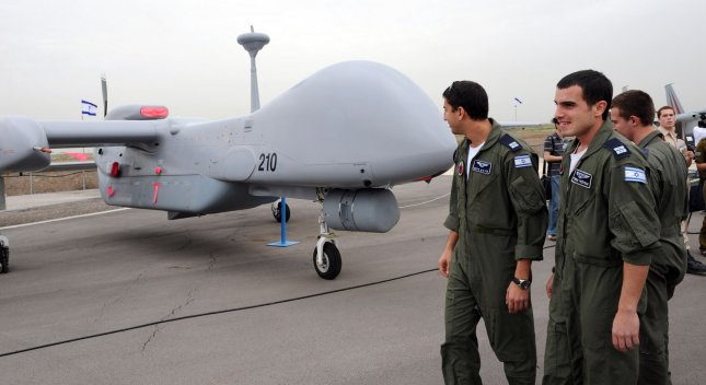 Israeli Air Force soldiers look at an Israeli made unmanned aerial vehicle, the Heron TP, at the drone's induction ceremony into the Israeli Air Force at the Tel Nof Air Force Base, February 21, 2010. The large drone is built by the Israel Aerospace Industries, IAI, and is capable of flying to Iran. It has a wingspan of 86 feet, the size of a passenger jet and can fly 20 consecutive hours. The drone is primarily used for surveillance and carrying payloads. UPI/Debbie Hill