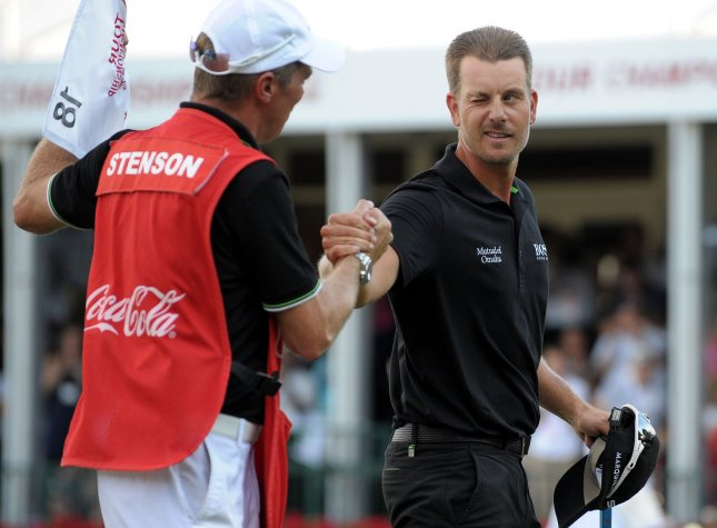 Henrik Stenson (R), shown with his caddie after winning the PGA Tour Championship in September, owns a one-stroke lead at the halfway point of the European Tour's DP World Tour Championship in the United Arab Emirates. Stenson shot an 8-under-par 64 in the Friday's second round. UPI/David Tulis