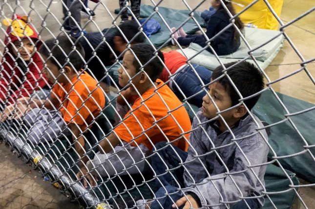 Detained children look into the United States on July 13 at a migrant processing center in McAllen, Texas. Photo courtesy Office of Rep. Doris Matsui/UPI