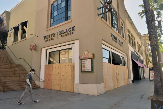 A man walks near a business on April 16 in Pasadena, Calif., that has been boarded up and closed due to coronavirus-related restrictions. Photo by Jim Ruymen/UPI