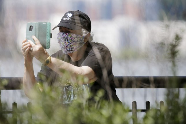 A woman takes a photo while wearing a protective face mask on a sidewalk on the Upper West Side of Manhattan New York City in May. Photo by John Angelillo/UPI