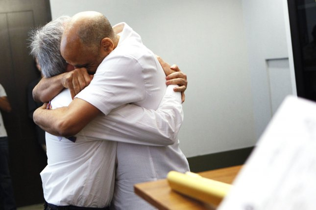 Same-sex couple Douglas Robinson (R) and Michael Elsasser embrace after being married at the City Clerk's Office in New York July 24, 2011.UPI/Shannon Stapleton/Pool