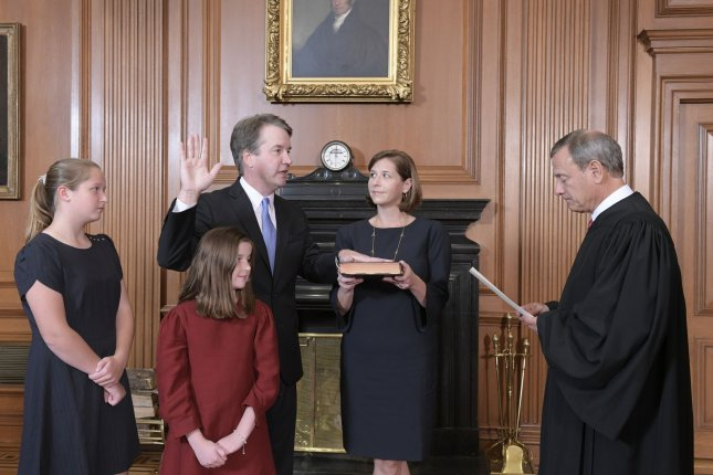 Chief Justice John G. Roberts, Jr. (R) administers the Constitutional Oath to Judge Brett M. Kavanaugh in the Justices' Conference Room, Supreme Court Building on Saturday in Washington D.C. Kavanaugh's wife Ashley holds the Bible as the couple's daughters Margaret, 13, and Elizabeth, 10, watch. Photo by Fred Schilling/Collection of the Supreme Court of the United States/UPI