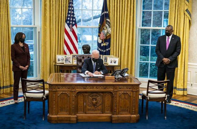 President Joe Biden (C), joined by Vice President Kamala Harris (L) and Defense Secretary Lloyd Austin, signs an executive order reversing a Trump era ban on transgender serving in the military, in the Oval Office at the White House on Monday. Pool Photo by Doug Mills/UPI