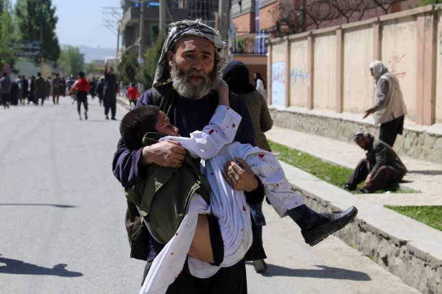 A man carries a wounded child at the site of a suicide bombing in Kabul , Afghanistan, on April 22, 2018. File Photo by Ezatullah Alidost/UPI