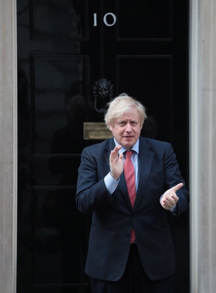 British Prime Minister Boris Johnson claps outside Downing Street in London to show his support for key workers during the coronavirus pandemic on Thursday. The British government is expected to institute a 14-day quarantine for international travelers. Photo by Hugo Philpott/UPI