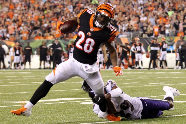 Cincinnati Bengals running back Joe Mixon (28) is tackled by Baltimore Ravens' Marlon Humphrey (29) during the first half of play on Thursday at Paul Brown Stadium in Cincinnati. Photo by John Sommers II/UPI