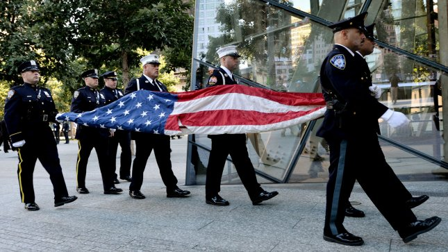 Port Authority Police Officers carry the American flag that flew over at the World Trade Center towers during anniversary ceremonies at the site of the World Trade Center, on September 11, 2012 in New York. UPI/Justin Lane/Pool