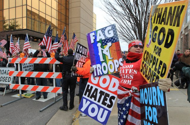 Two members from the Westboro Baptist Church of Topeka, Kansas, chant on a street corner in St. Charles, Missouri while those disagreeing with their views, are kept back by police and barriers on January 6, 2011. The church which preaches against all form of sin, is known for showing up at military funerals to drive home their anti-gay point. St. Charles County has passed a law that the Westboro Baptist Church demonstrators must be atleast 300 feet from any military funeral or burial. The law is now being challanged in Federal court by the ACLU. UPI/Bill Greenblatt