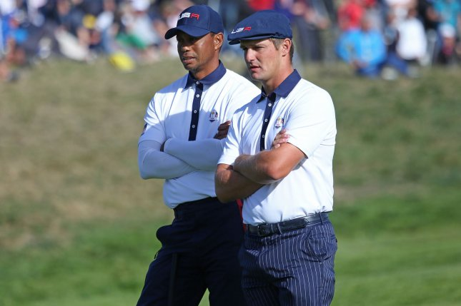 Tiger Woods (L) and Bryson DeChambeau watch Tommy Fleetwood putt on the 9th green on day two of the Ryder Cup on Saturday at Le Golf National in Guyancourt near Paris. Photo by David Silpa/UPI