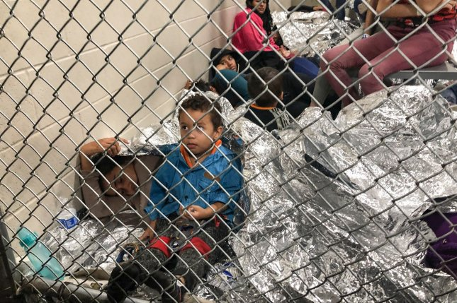Women and children lie on the floor amid space blankets behind cyclone fencing at the Central Processing Center in McAllen, Texas ,on July 13. File Photo courtesy of U.S. Rep. Doris Matsui's office