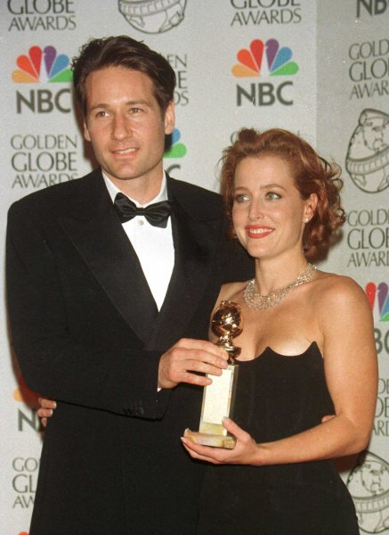 David Duchovny and Gillian Anderson, who costar in the television series The X Files, pose with the Golden Globe the show won for best drama series January 18,1998, at the 5th annual Golden Globe Awards. The series debuted September 10, 1993, on Fox. File Photo by Jim Ruymen/UPI