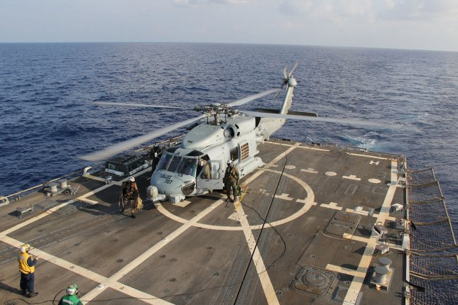 A U.S. Navy MH-60R Sea Hawk helicopter from Helicopter Maritime Strike Squadron (HSM) 78, Det 2, assigned to the guided-missile Destroyer USS Pinckney (DDG 91), lands during a crew swap before returning to the search and rescue for the missing Malaysian airlines flight MH370, March 10, 2014. (File/UPI/Chris D. Boardman/US Navy)