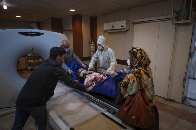 An Iranian medical working wearing protective gear helps a patient undergo a CT scan at the Rassolakram hospital in western Tehran in March.  Photo by Morteza Nikoubazl/UPI