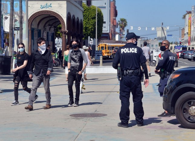 Beachgoers with face masks walk past policemen upon arriving the Venice Beach boardwalk in Los Angeles on Friday, as city and county officials said residents must wear face coverings when going outdoors. Photo by Jim Ruymen/UPI