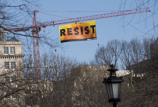 Seven protesters who climbed a construction crane to protest President Donald Trump were arrested Wednesday night after they descended from the crane. They displayed a large banner reading Resist, visible from the White House. Photo by Kevin Dietsch/UPI