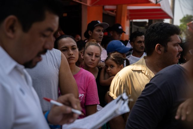 A crowd forms as names are called outside of the National Institute of Migration in Tapachula, Mexico on May 6. Photo by Ariana Drehsler/UPI