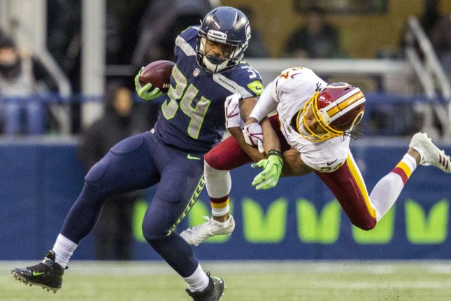 Washington Redskins cornerback Josh Norman (24) hangs onto Seattle Seahawks running back Thomas Rawls (34) as Rawls rushes for a 7-yard gain during the fourth quarter in their game on Sunday at CenturyLink Field in Seattle. Photo by Jim Bryant/UPI