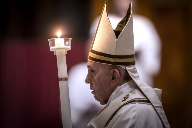 Pope Francis holds a candle as he presides over Easter's Holy Saturday Vigil held behind closed doors at St. Peter's Basilica in the Vatican on Saturday, April 11, 2020, during the lockdown aimed at curbing the spread of the COVID-19 infection. Pool Photos by Possolo/Spaziani/UPI